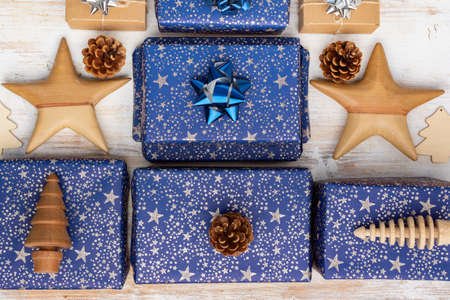 Creative christmas composition. Presents in dark blue wrapping paper with silver stars and sparkles, wooden decorations, ornaments, paper tags on white table, top view, selective focus