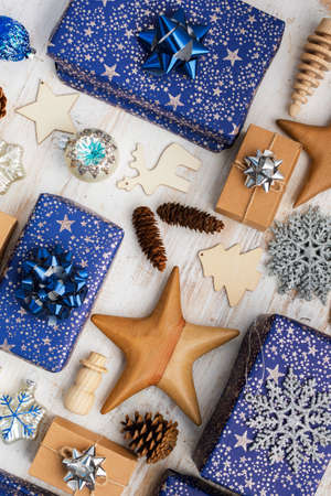 Creative christmas composition. Presents in blue wrapping paper with silver sparkles, wooden decorations, ornaments on white table, top view, selective focus