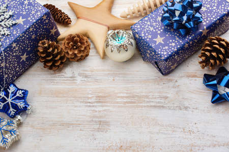 Christmas background. Presents in blue wrapping paper with silver sparkles, wooden decorations, ornaments on white table, selective focus Stock Photo