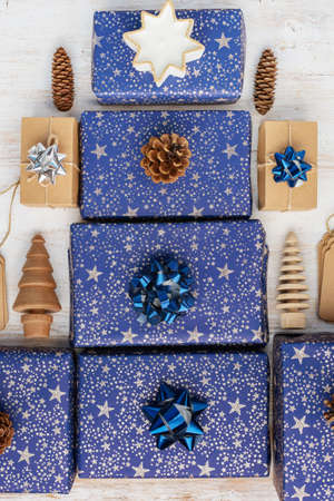 Presents in dark blue wrapping paper with silver stars and sparkles and wooden decorations Stock Photo