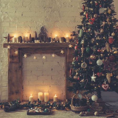Beautiful Christmas setting, decorated fireplace with solid wood mantelpiece, lit up Christmas tree with baubles and ornaments, stars, Christmas lights, candles, toned, selective focus