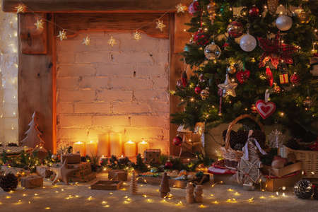 Magical Christmas setting, decorated fireplace with wooden mantelpiece fire surround, lit up Christmas tree with baubles ornaments, stars, lights, candles, lightly toned, selective focus Stock Photo
