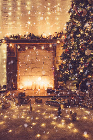 Beautiful Christmas with created snow, decorated fireplace with wood mantelpiece, lit Christmas tree with baubles and ornaments, stars, Christmas lights, candles,vintage effect, toned, selective focus Stock Photo