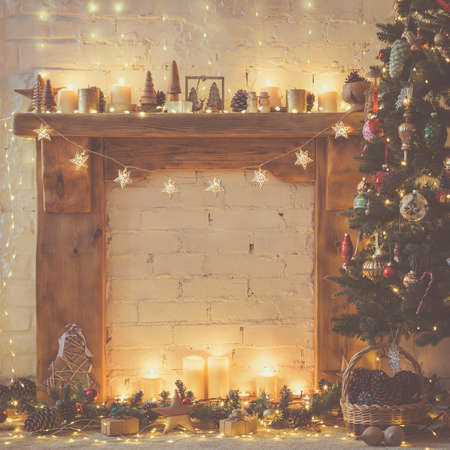 Beautiful Christmas backgroun, decorated fireplace with solid wood mantelpiece, lit up Christmas tree with baubles and ornaments, stars, Christmas lights, candles, toned, selective focus