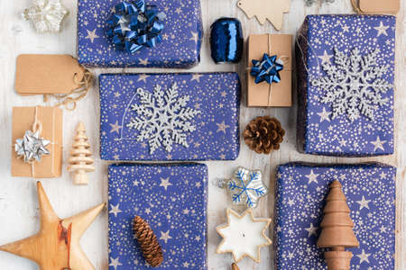 Creative chritmas composition background. Presents in dark blue wrapping paper with silver stars and sparkles, wooden decorations, ornaments, paper tags and pinecones on white table, top view