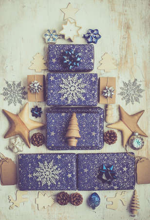 Creative Chritmas composition. Presents in blue wrapping paper with silver, wooden decorations, ornaments, gift tags and pine cones arranged in shape of Christmas tree on white table, top view, toned Stock Photo