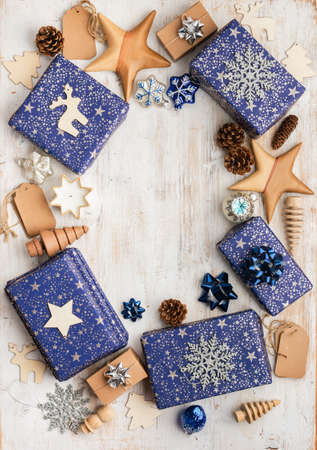 Creative chritmas composition. Presents in blue wrapping paper with silver sparkles, wooden decorations, ornaments on white table, copy space in the middle, top view, selective focus
