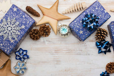 Chritmas background. Presents in blue wrapping paper with silver sparkles, wooden decorations, ornaments on white table, selective focus Stock Photo
