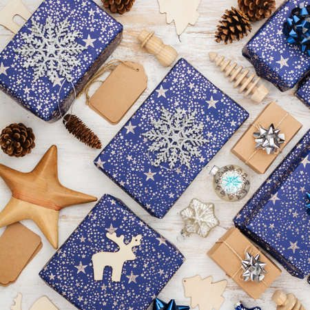 Creative chritmas composition. Presents in blue wrapping paper with silver sparkles, wooden decorations, ornaments on white table, top view, selective focus