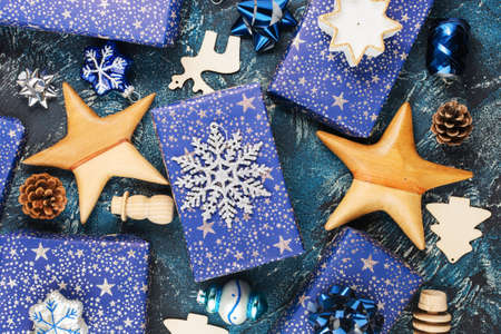 Creative chritmas composition background. Presents in dark blue wrapping paper with silver stars sparkles, wooden decorations, ornaments, baubles and pinecones on blue table, top view