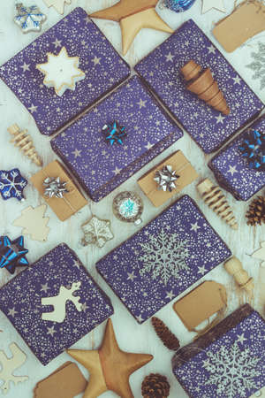 Creative chritmas composition. Presents in blue wrapping paper with silver sparkles, wooden decorations, ornaments on white table, top view, toned, selective focus