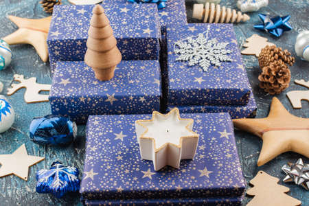 Chritmas composition. Presents in dark blue wrapping paper with silver stars sparkles, wooden decorations, ornaments, baubles on blue table, selective focus