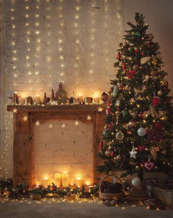 Schöne Weihnachtseinstellung, Kamin mit Kaminfeuereinfassung aus Holz, beleuchteter, dekorierter Weihnachtsbaum mit Kugeln und Ornamenten, Sternen, Weihnachtsbeleuchtung, Kerzen, selektiver Fokus Standard-Bild