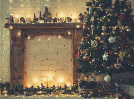 Beautiful Christmas background, decorated fireplace with solid wood mantelpiece, lit up Christmas tree with baubles and ornaments, stars, Christmas lights, candles, selective focus