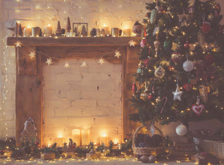 Beautiful Christmas setting, decorated fireplace with solid wood mantelpiece, lit up Christmas tree with baubles and ornaments, stars, Christmas lights, candles, selective focus