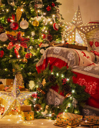 Christmas living room, decorated fireplace with wood mantelpiece, lit up Christmas tree with baubles, stars, pine cones, cosy armchair with read throw, wooden ornaments, wreath, selective focus