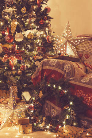 Christmas living room, decorated fireplace with wood mantelpiece, lit up Christmas tree with baubles, stars, pine cones, cosy armchair with read throw, wooden ornaments, wreath, toned, selective focus Stock Photo