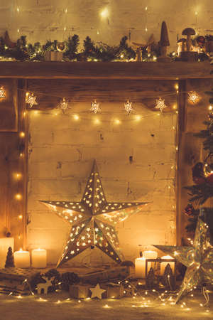 Beautiful decorated wood mantelpiece, lit up Christmas tree with baubles and ornaments, wooden decorations, silver star, icicle lights, toned, selective focus