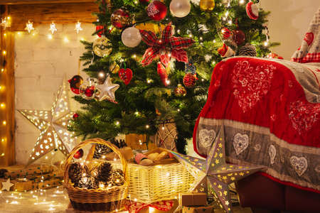 Christmas living room, decorated fireplace with wood mantelpiece, lit up Christmas tree with baubles, stars, pine cones, cosy armchair with read throw, wooden ornaments, selective focus