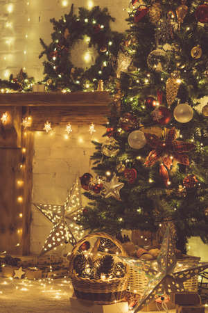 Beautiful warm interior, decorated fireplace with solid wood mantelpiece, lit up Christmas tree with baubles and ornaments, stars and lights, candles. handmade wreath, toned, selective focus