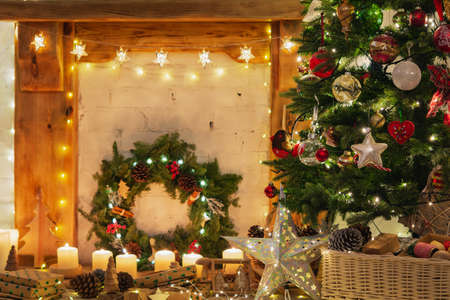 Beautiful Christmas setting, decorated fireplace with wooden mantelpiece fire surround, lit up Christmas tree with baubles ornaments, stars, lights, candles, vintage effect selective focus