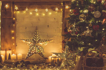 Beautiful wood mantelpiece, lit up Christmas tree with baubles and ornaments, wooden decorations, silver star, icicle lights, toned, selective focus