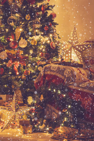 Christmas lounge, decorated fireplace with wood mantelpiece, lit up Christmas tree with baubles, stars, cosy armchair with read throw, wooden ornaments, wreath, toned, created snow, selective focus