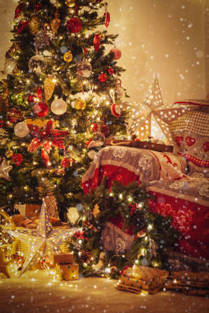 Living room, decorated fireplace with wood mantelpiece, lit Christmas tree with baubles, stars, pine cones, cosy armchair with read throw, wooden ornaments, wreath, created snow, selective focus Stock Photo