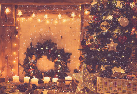 Magical Christmas setting, decorated fireplace with wooden mantelpiece fire surround, lit up Christmas tree with baubles ornaments, stars, lights, candles, toned, created snow, selective focus