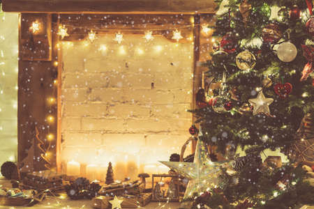 Christmas setting, decorated fireplace, wooden mantelpiece fire surround, lit up Christmas tree with baubles ornaments, stars, candles, toned, vintage effect, created snow, selective focus Stock Photo