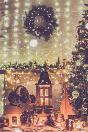 Wooden toys, figures, stars, moose, fur tree lantern on table in front of fireplace, decorated mantel, Christmas tree with baubles, ornaments, lights candles, created snow, selective focus, toned