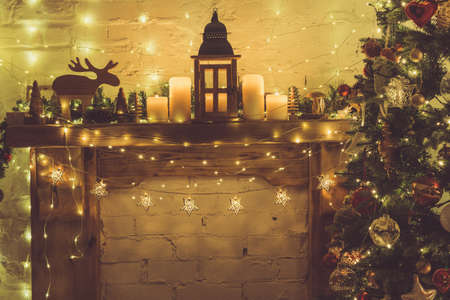 Magical Christmas setting, decorated fireplace with wooden mantelpiece fire surround, lit up fur tree with baubles, stars, lights, lantern and candles, lightly toned, selective focus
