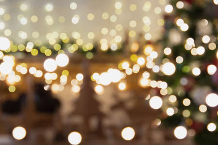 Abstract composition. Beautiful blurred Christmas interior with fireplace, wood mantelpiece, lit up Christmas tree, warm yellow and colorful lights, candles, toned