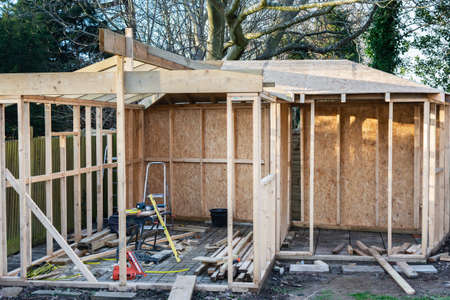 Project of wooden summer house, log cabin or shed, unfinished structure with stone base, selective focus