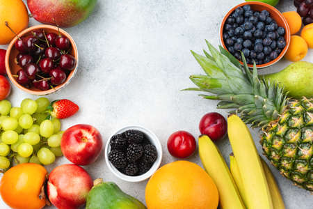 Healthy fruits, strawberries bananas plums apples apricots grapes blueberries cherries persimmon on the white table, top view, copy space for text, selective focus