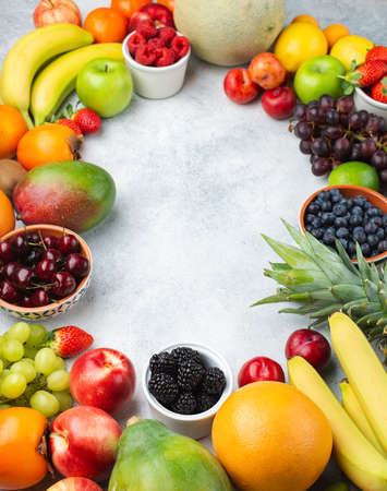 Healthy fruit background frame, strawberries raspberries oranges plums apples kiwis grapes blueberries mango persimmon on the white table, copy space for text, selective focus Stock Photo
