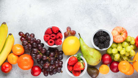 Top view of delicious fruits, raspberries oranges plums apples pears grapes blueberries bananas strawberries on white table, top view, copy space for text, selective focus Stock Photo