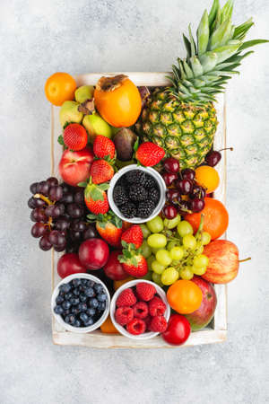 Healthy fruits in a wooden tray, strawberries raspberries oranges plums apples kiwis grapes blueberries mango persimmon pineapple on the white table, top view, copy space for text, selective focus