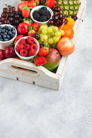 Healthy fruits in wooden tray, strawberries raspberries oranges plums apples kiwis grapes blueberries mango persimmon pineapple on the white table, copy space for text, selective focus