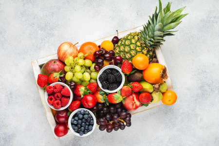Rainbow fruits in wooden tray, strawberries raspberries oranges plums apples kiwis grapes blueberries mango persimmon pineapple on the white table, top view, copy space for text, selective focus