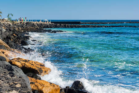 Turquoise waters in Las Cucharas beach, Lanzarote, Canary islands. VIew of the sea, sandy beach and rocks, selective focus 免版税图像