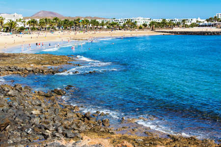 Golden sand and volcanic rocks at Las Cucharas beach, Lanzarote, Canary islands. VIew of the sea, coast and rocks, selective focus