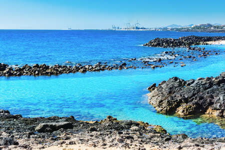Lagoon with turquoise clear water in Playa Jablillo beach, in Costa Teguise, Lanzarote, Canary islands. Sandy beach with blue sea, volcanic rocks, selective focus 스톡 콘텐츠