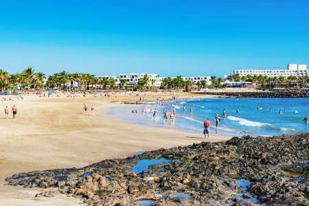 COSTA TEGUISE, LANZAROTE - 26 December 2018. People in Las Cucharas beach, Lanzarote, Canary islands. VIew of the sea, sandy beach and mountains, selective focus