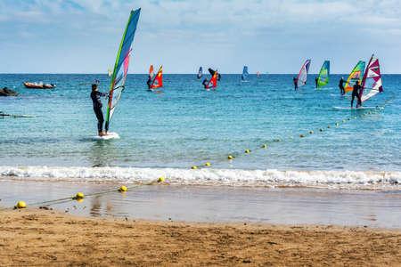 COSTA TEGUISE, LANZAROTE - 27 December 2018. Surfers in blue sea in Las Cucharas beach, Canary islands, selective focus
