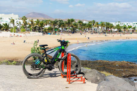 COSTA TEGUISE, LANZAROTE - 27 December 2018. Bikes in Las Cucharas beach, Canary islands. VIew of the sea, sandy beach and mountains, selective focus