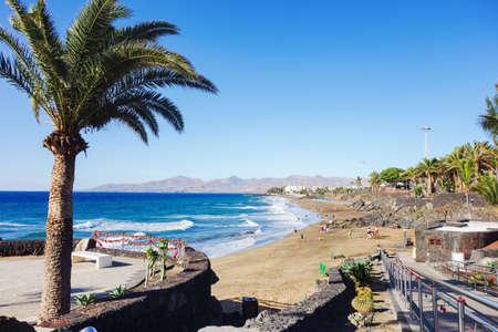 PUERTO DEL CARMEN, LANZAROTE - 23 December 2018. Puerto del Carmen beach in Lanzarote, Canary islands, Spain. blue sea, palm trees, selective focus Editorial