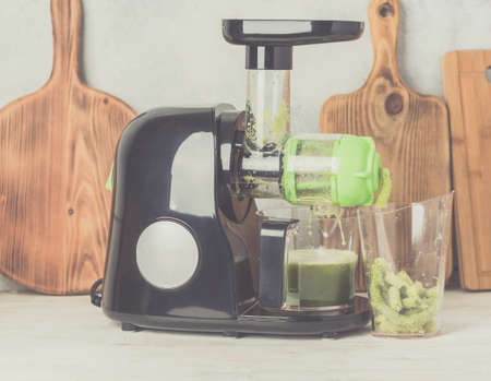 Slow masticating juicer producing healthy celery juice, extracting the pulp, on white table, healthy detox concept, selective focus