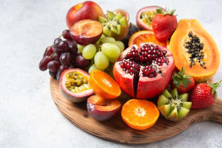 Delicious fruit platter pomegranate papaya oranges passion fruits on wooden board on white, selective focus Reklamní fotografie