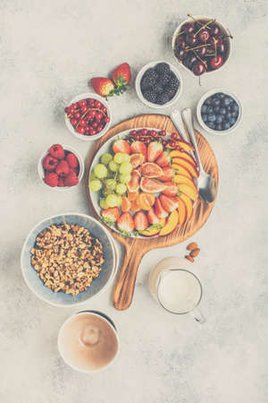 Raw vegan grain free paleo style granola or muesli made from nuts. Fruit berries platter, strawberries blueberries raspberries peach figs red currant, overhead view, toned, selective focus